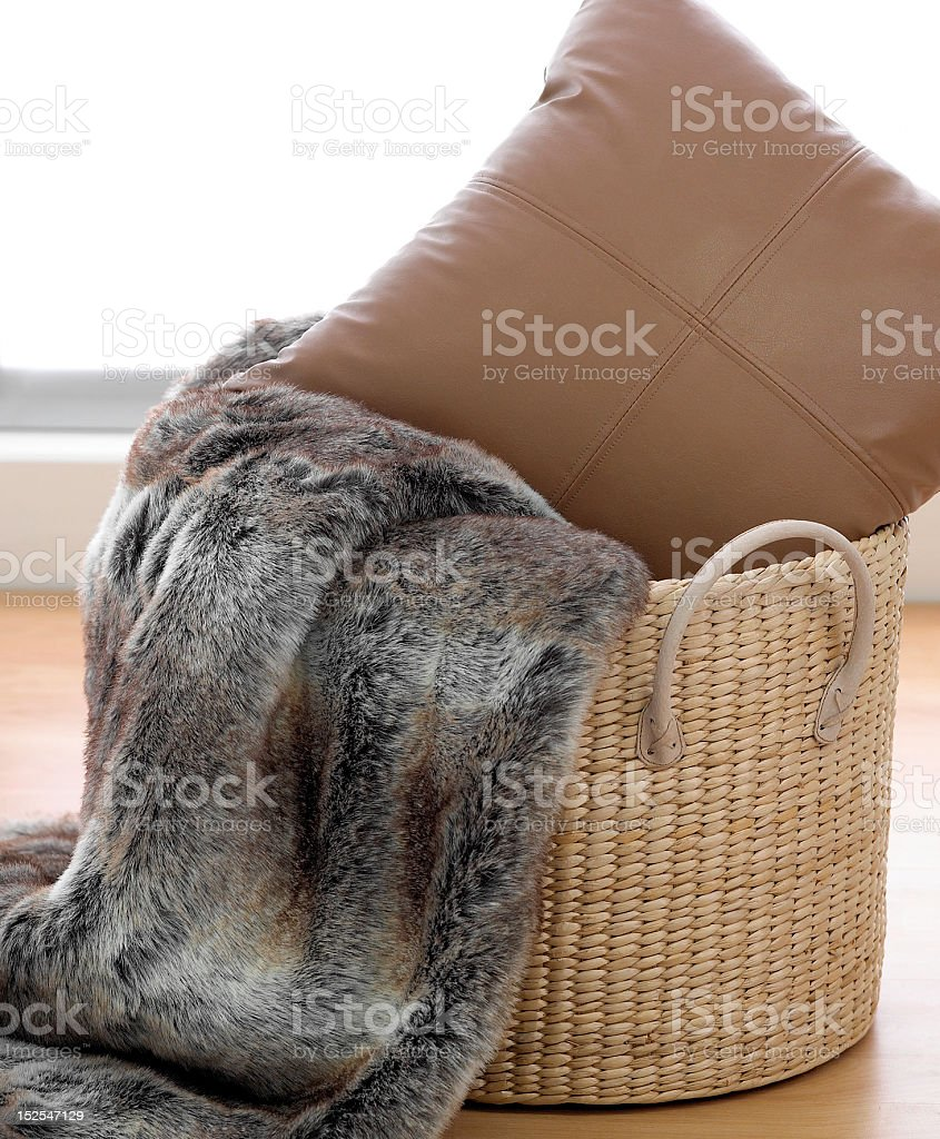 Fake fur rug with brown cushion in cane basket stock photo