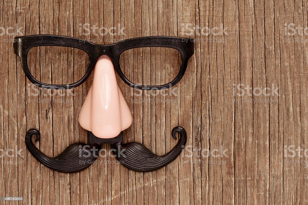 fake mustache, nose and eyeglasses on a wooden surface stock photo