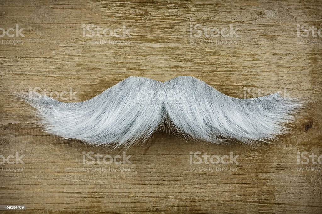 Fake mustache on an old wooden background stock photo