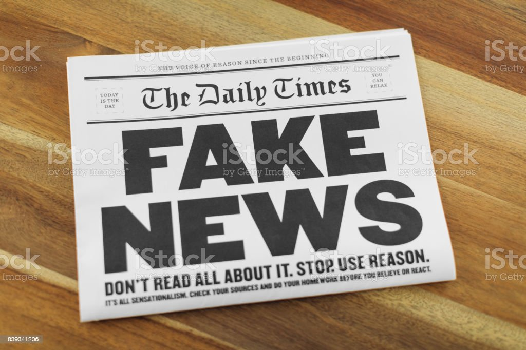 A newspaper publication with the headline Fake News sits folding on a...