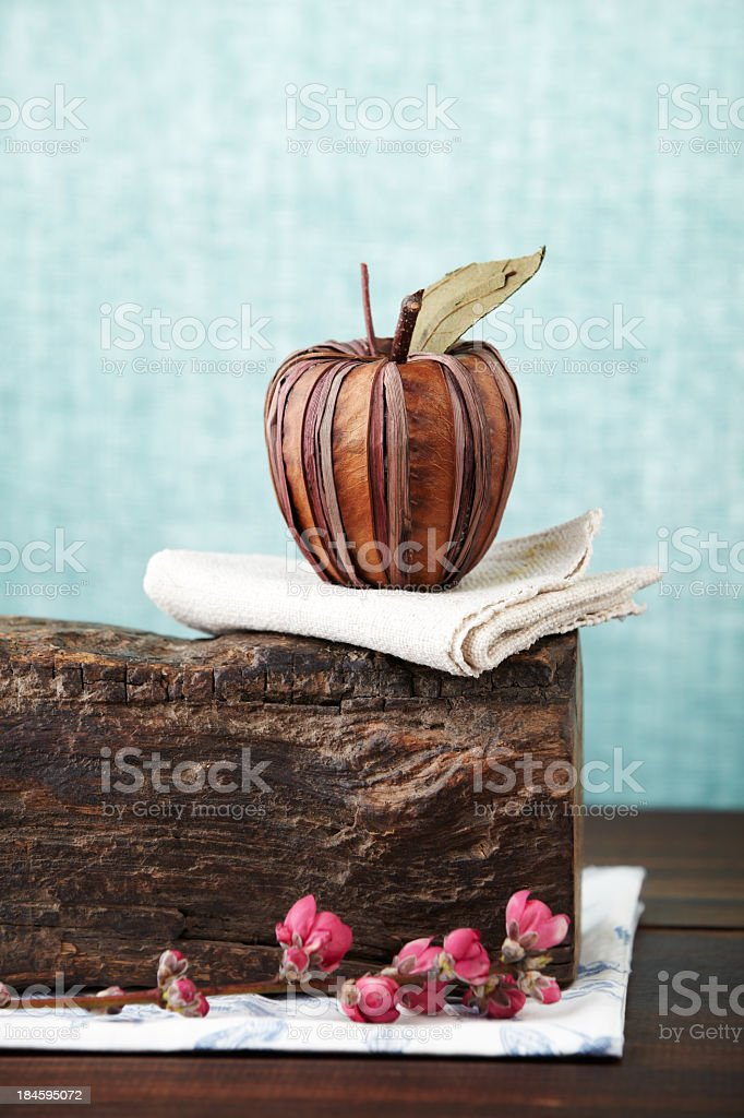 Fake red apple on wood block against blue background royalty-free stock photo