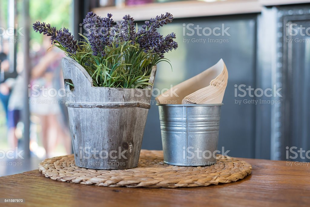 Faked flowers in wooden bucket and napkin paper in bucket stock photo