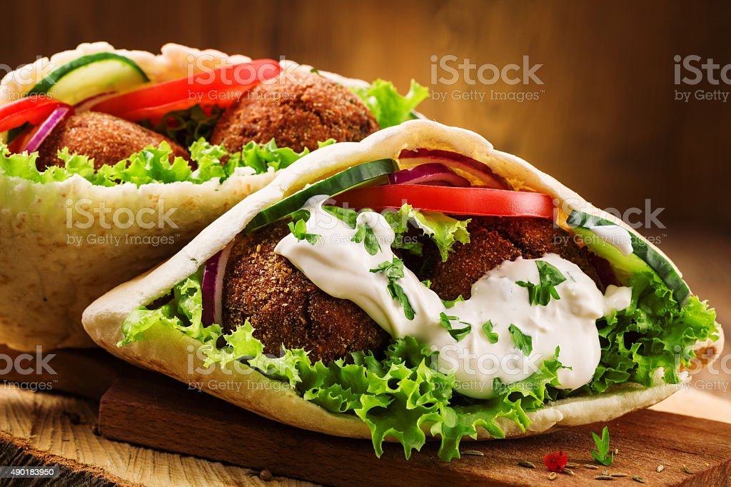 Falafel and fresh vegetables in pita bread on wooden table stock photo