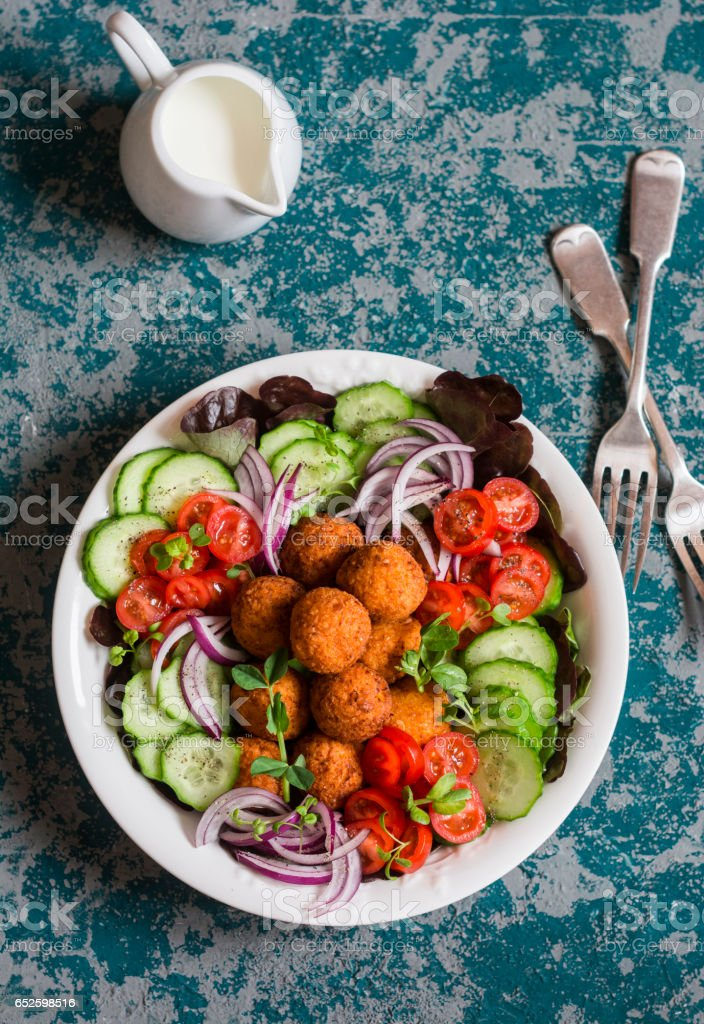 Falafel and vegetables salad bowl. Delicious vegetarian food concept. Buddha bowl on dark background, top view stock photo