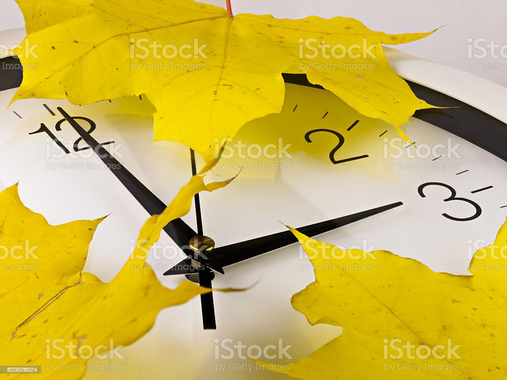 Fall back, winter time. Clock with yellow maple leaves. stock photo