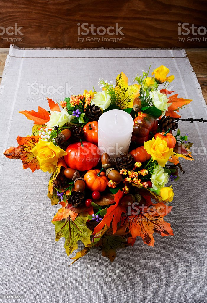 Fall decoration with candle and silk maple leaves vertical stock photo