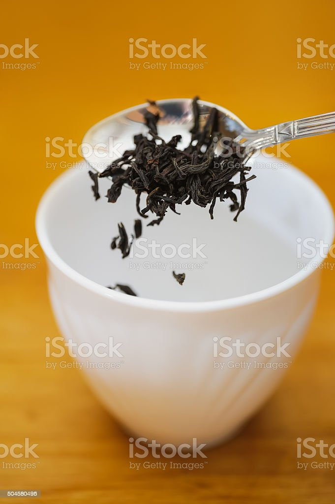 fall dried black tea into cup stock photo