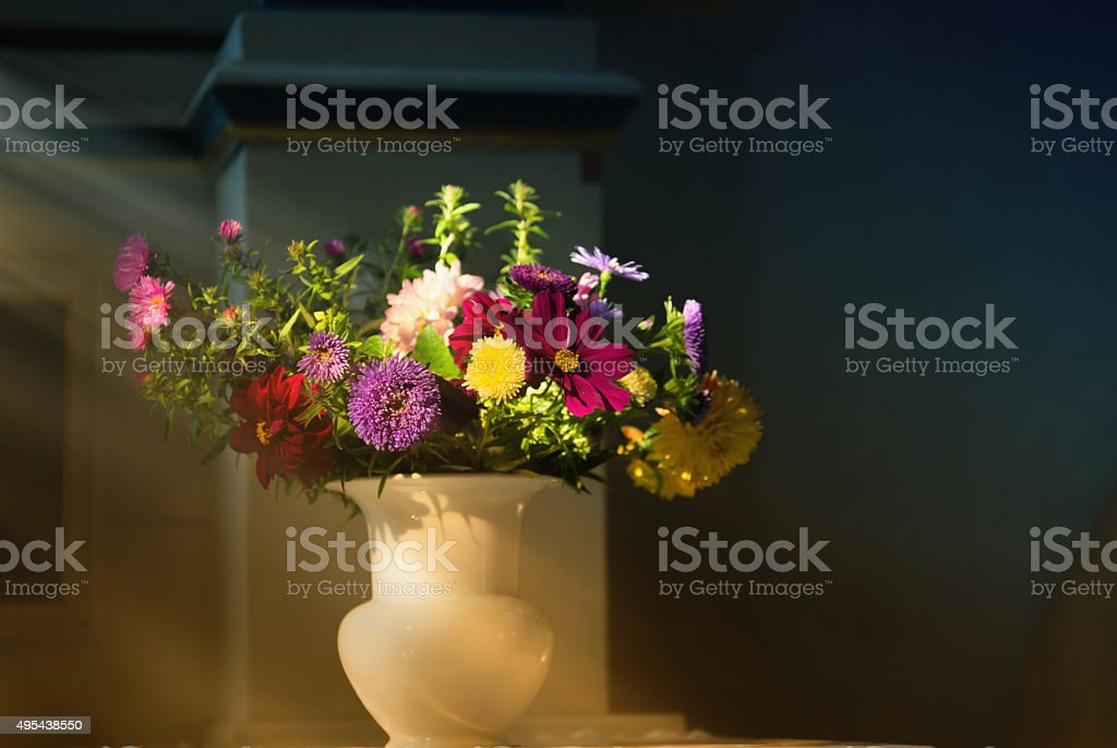 fall flowers at an altar in a church in light stock photo