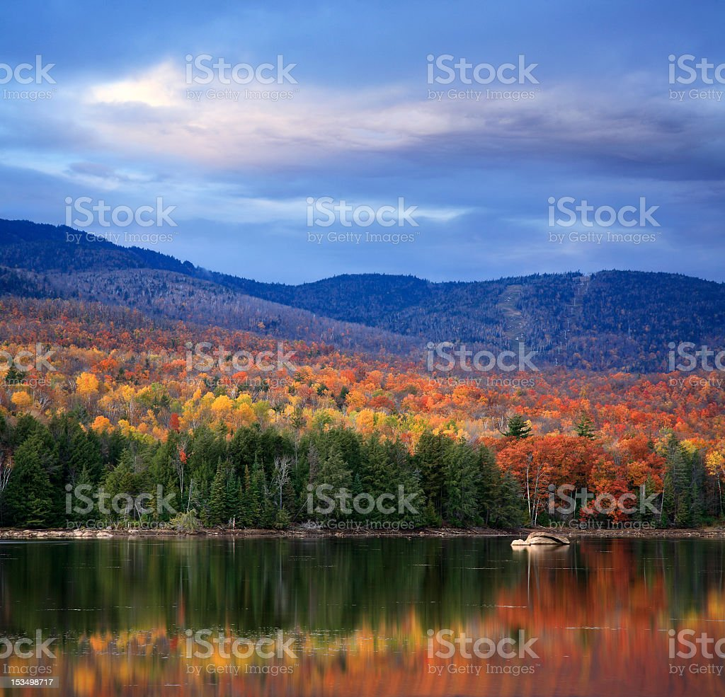 Fall mountainside reflecting in a lake stock photo