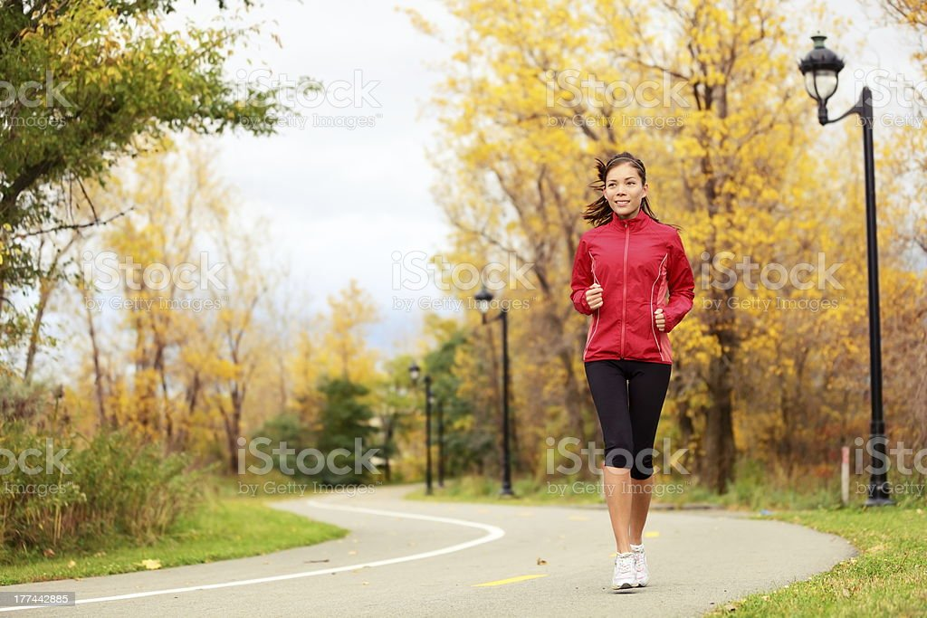 Fall running - woman jogging in autumn stock photo