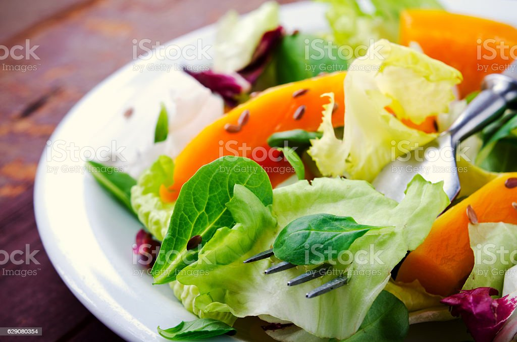 Fall salad with greens, arugula, flax seeds and roasted squash stock photo