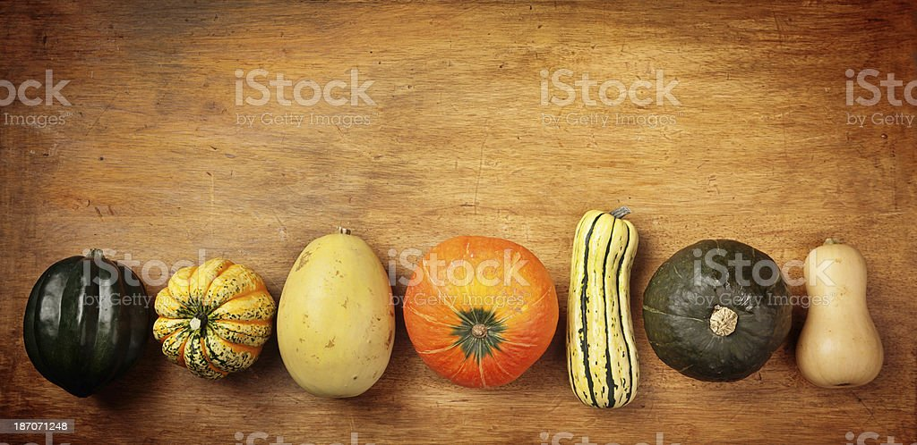 Fall Squash Vegetable Variety in Row on Rustic Wood Table stock photo
