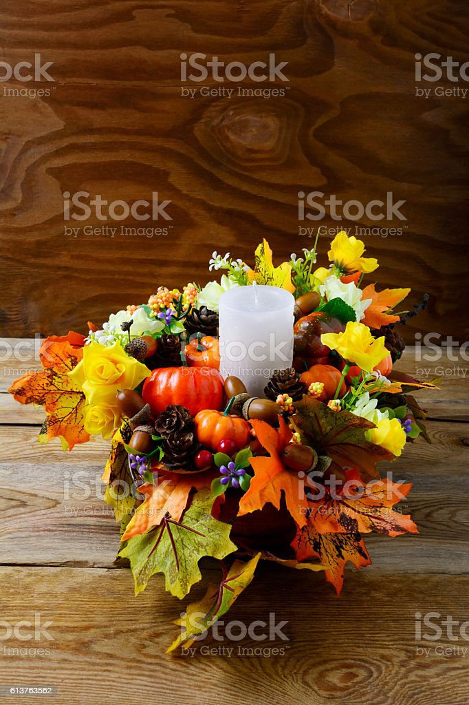 Fall table centerpiece with candle and silk maple leaves, vertic stock photo