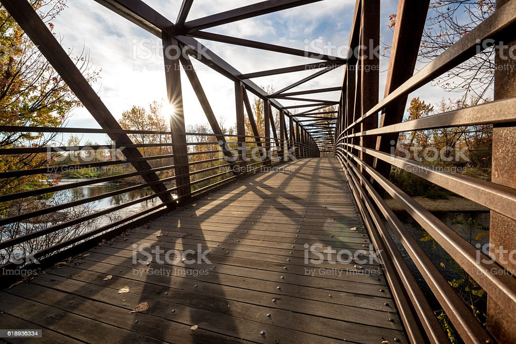 Fall trees and rusted foot bridge cross a river stock photo
