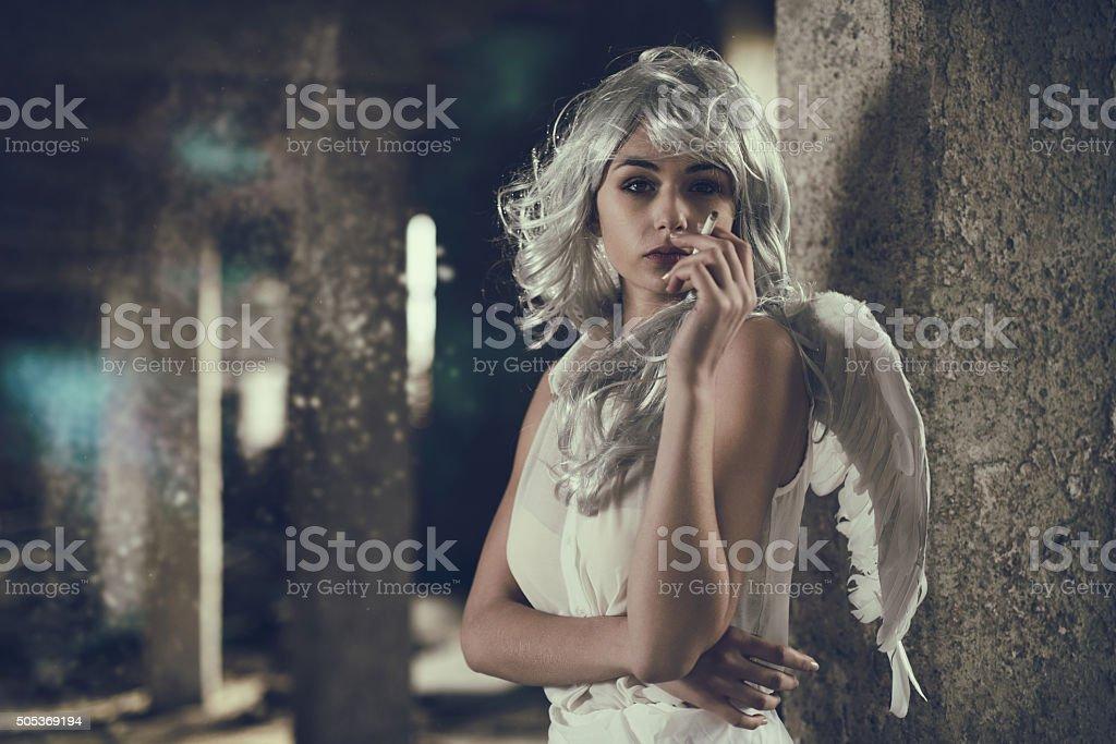 Fallen angel smoking a cigar in a ruin. stock photo