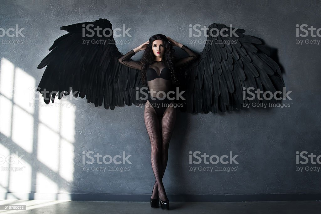Fallen black angel with wings. Sexual woman stock photo
