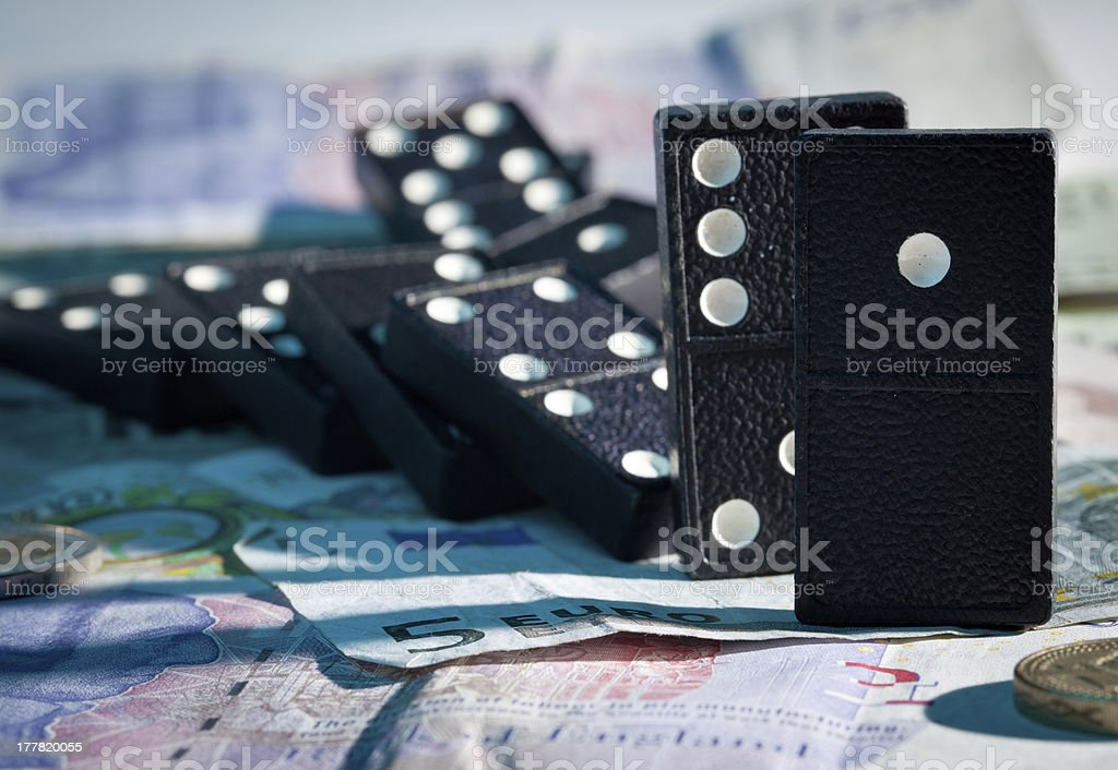 Fallen dominoes on bank notes stock photo