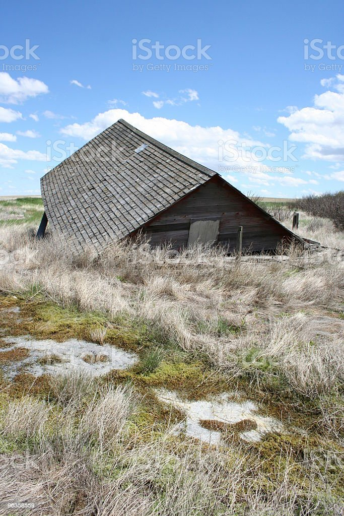 fallen farm building sags to the ground stock photo