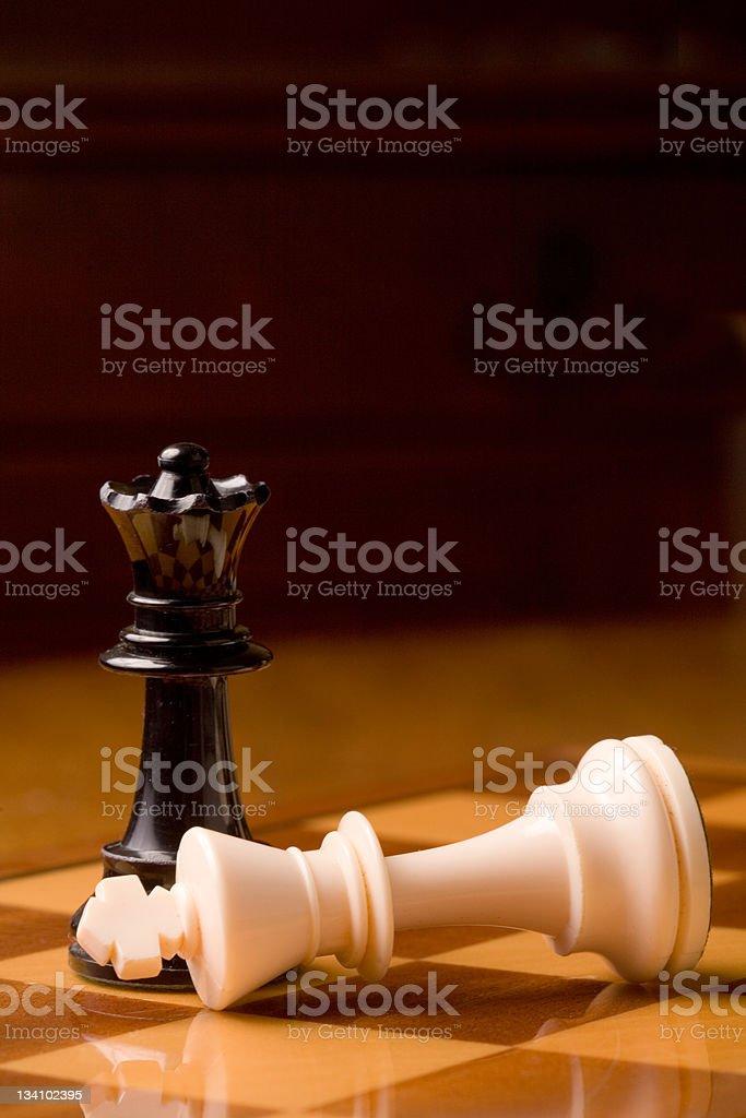Fallen king at foot of queen stock photo