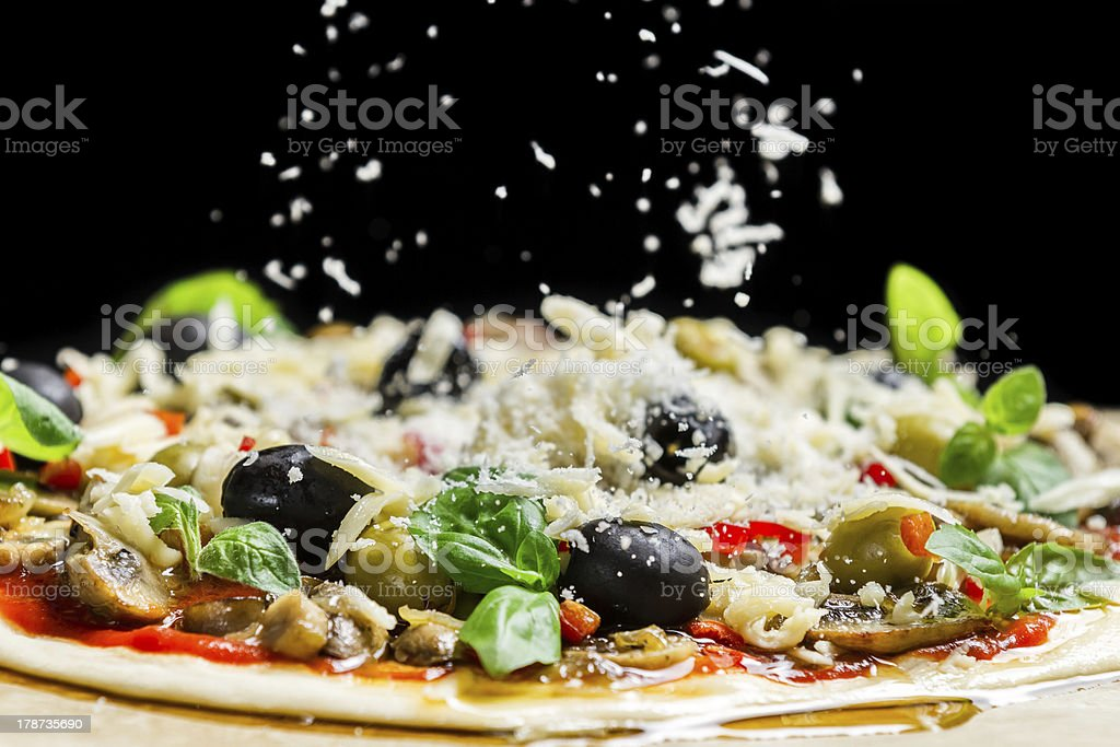 Falling cheese on a freshly prepared pizza with black olives stock photo