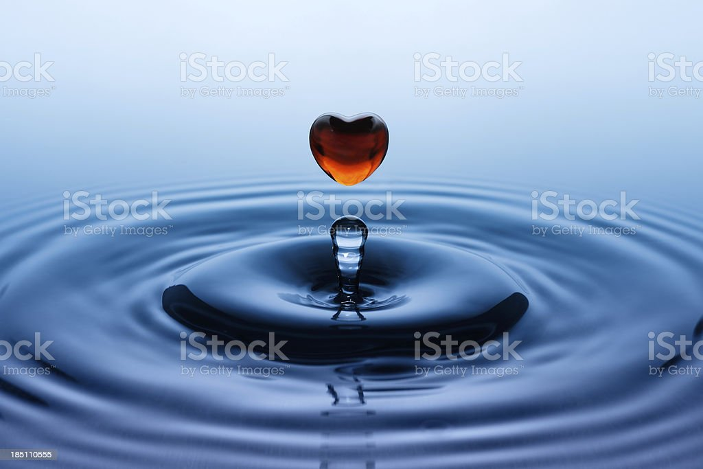 Falling down drop in heart shape stock photo
