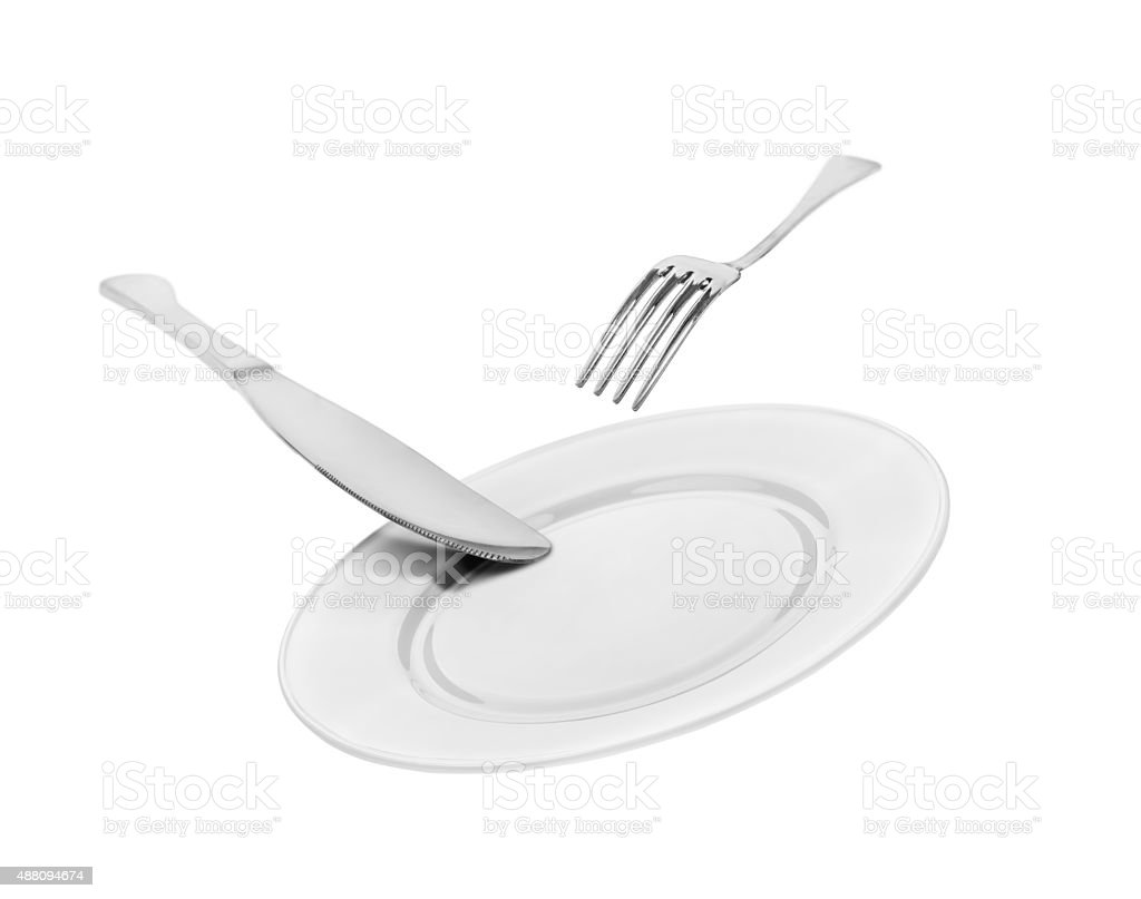 falling empty white plate, knife and fork isolated on white background stock photo
