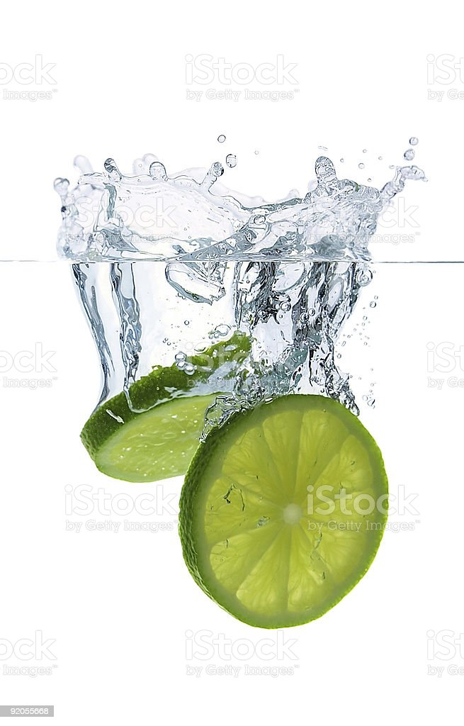 Falling lime slices with water splashes stock photo
