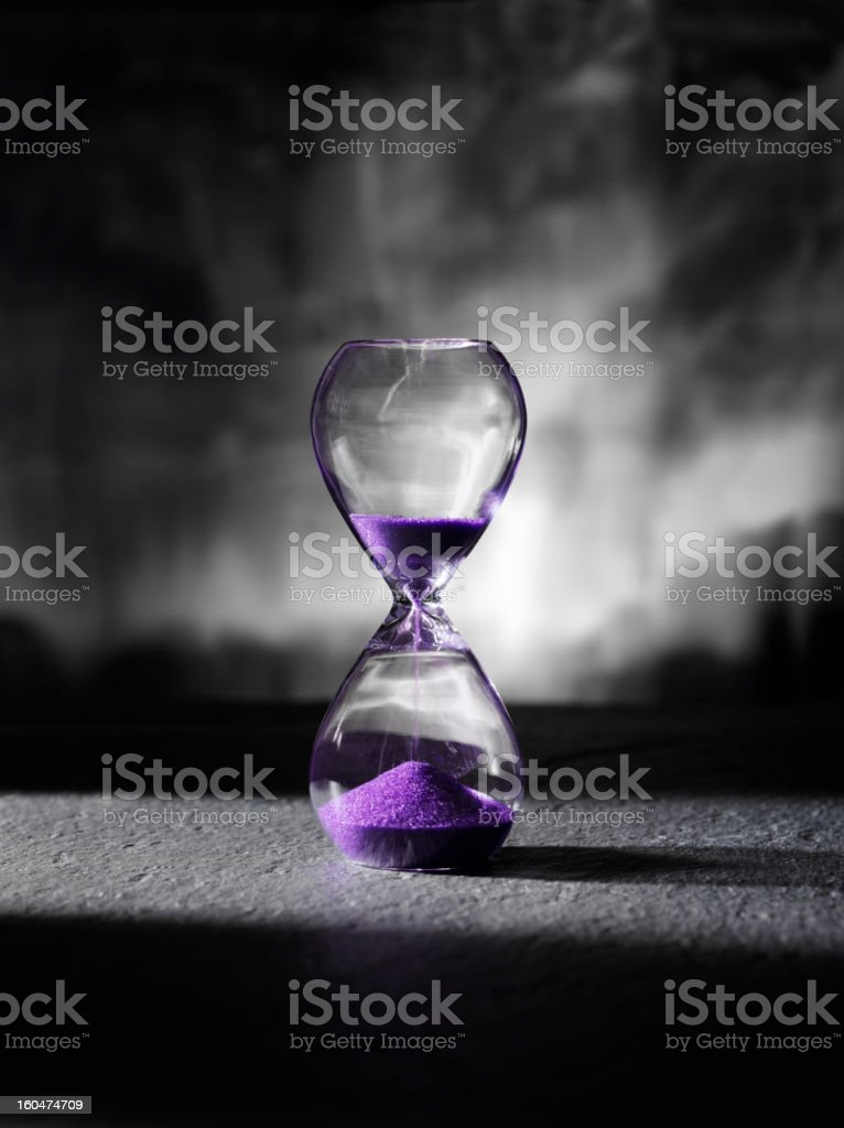 Falling Purple Sand in an Hourglass royalty-free stock photo