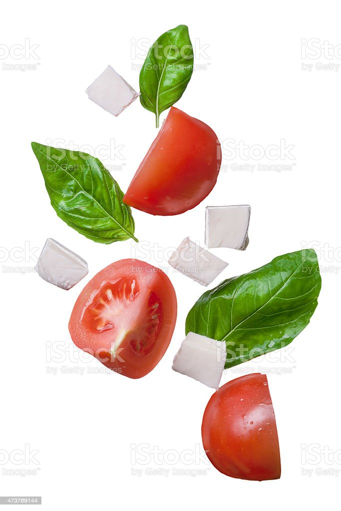 falling red tomatoes, mozzarella and basil isolated stock photo