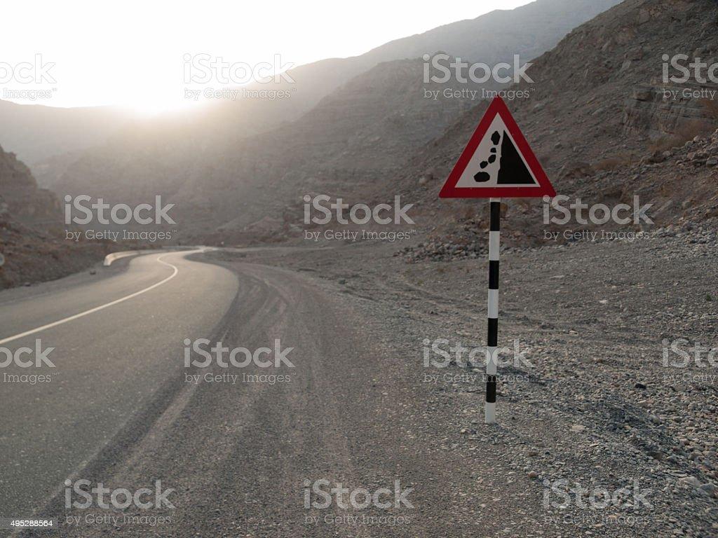 Falling rocks arabic road sign stock photo