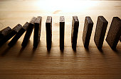 Falling row of dominoes on wooden surfaces