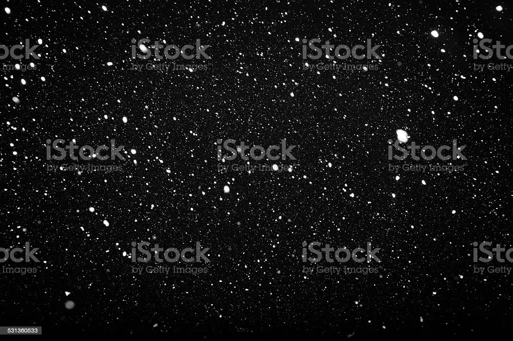 Falling snow on black background stock photo