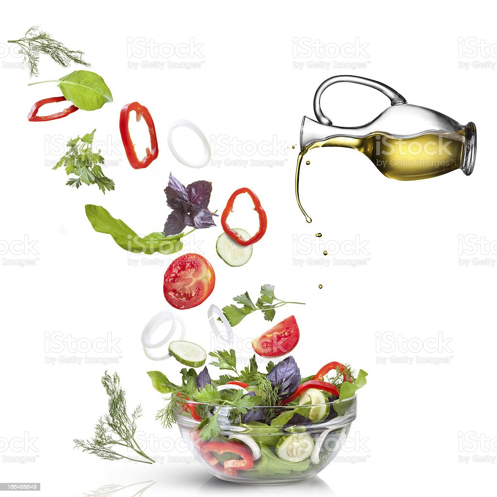 Falling vegetables for salad and oil isolated on white royalty-free stock photo