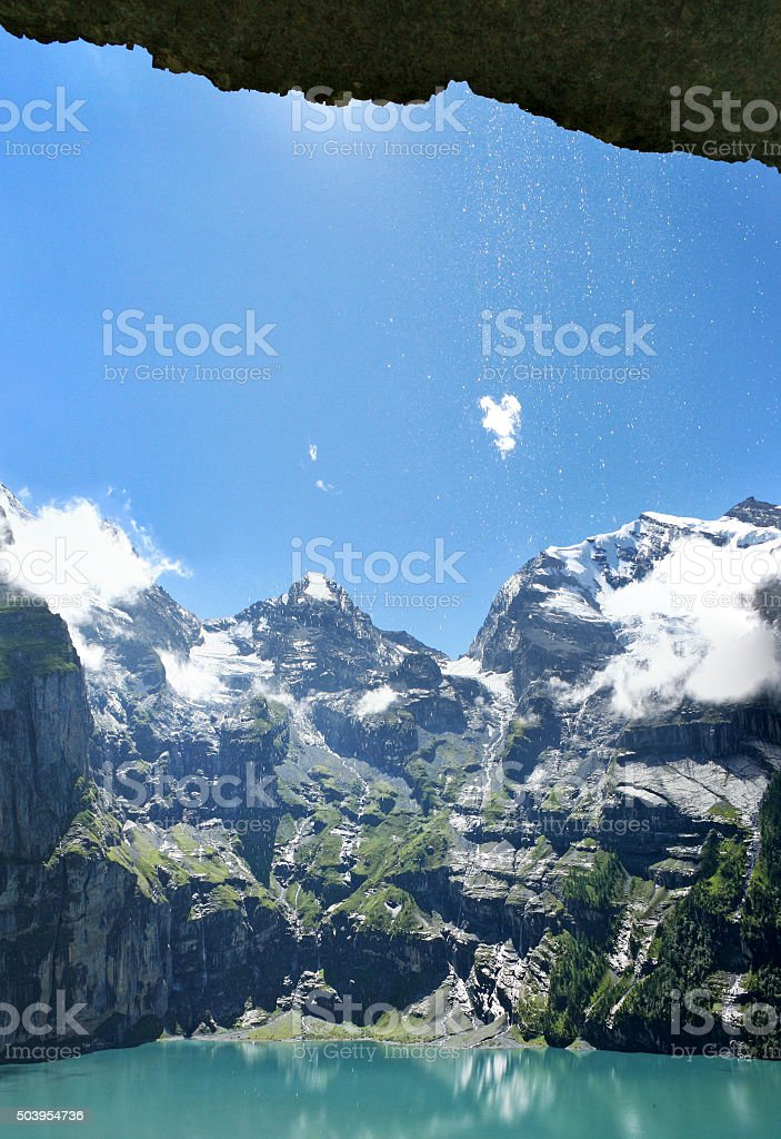 Falling water and a view on an alpine lake stock photo