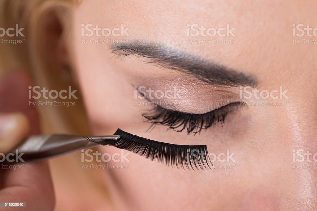False Eyelashes Being Put On Woman's Eye stock photo