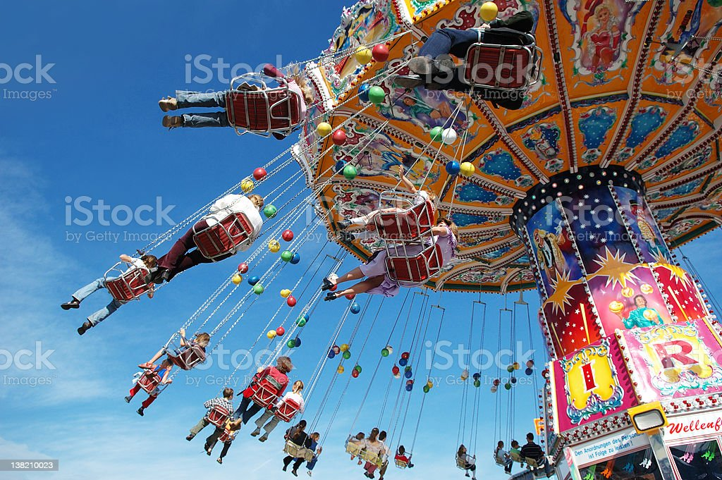 Families at the fair on a swing ride stock photo