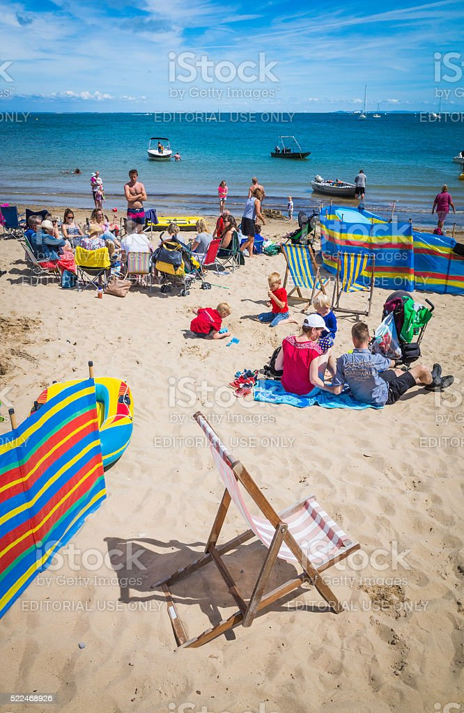 Families enjoying a day at the beach seaside deckchairs UK stock photo