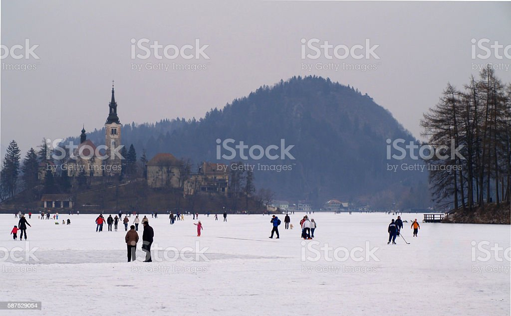 Families enjoying a frozen Lake Bled. stock photo