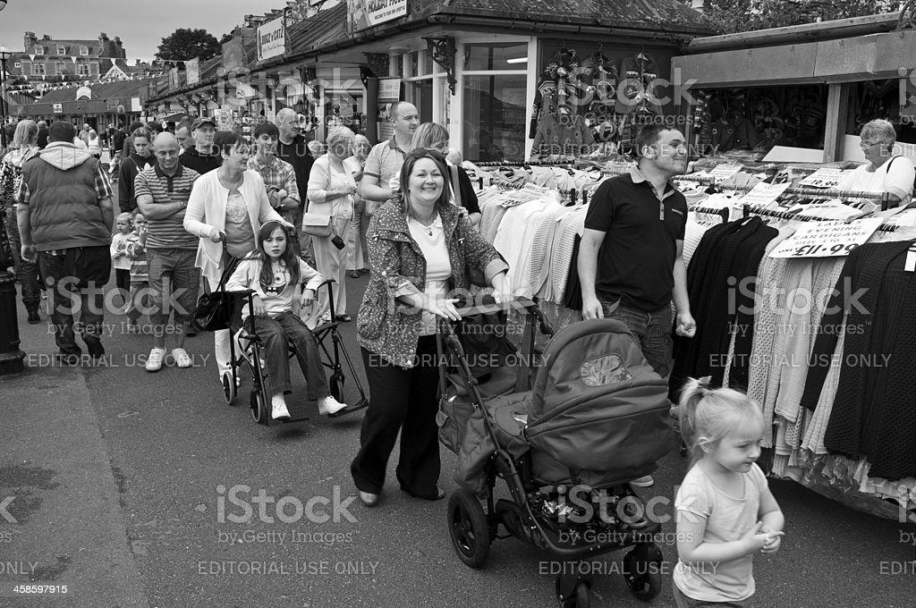 Families enjoying day at seaside promenade market stock photo