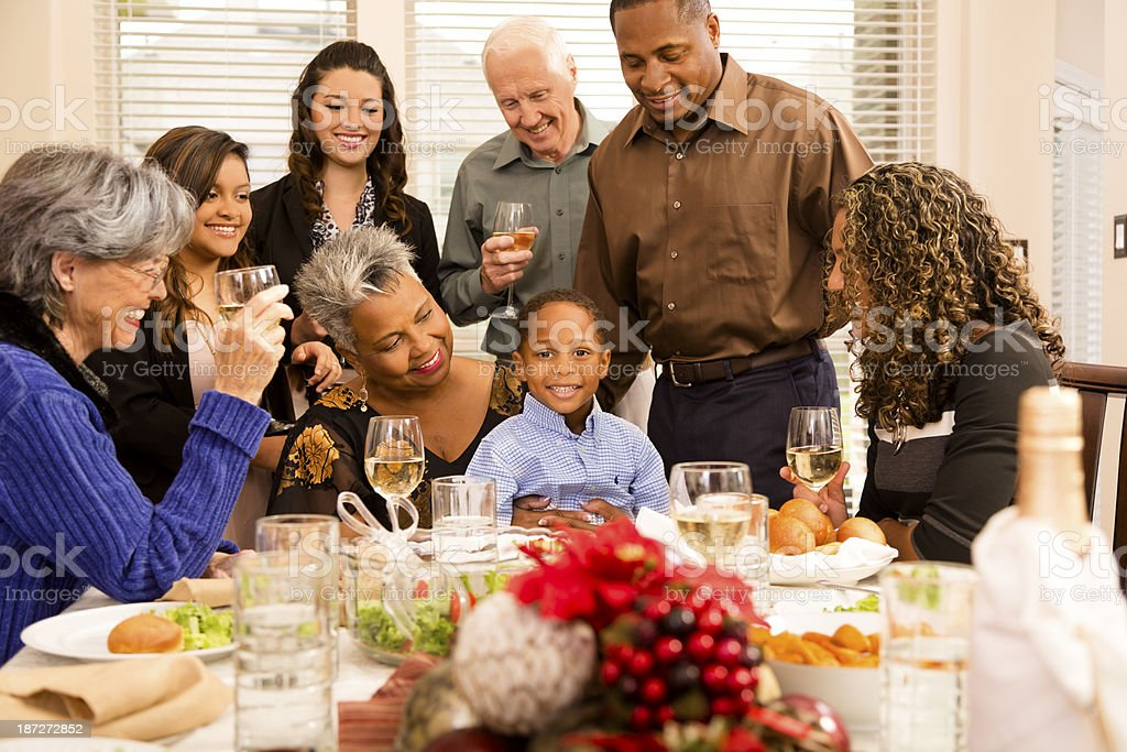 Multi-ethnic family and friends gather at senior woman\'s home for...