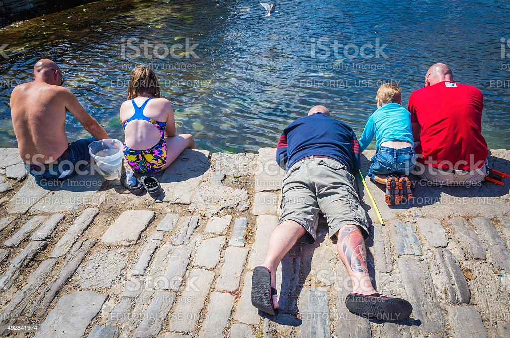 Families fathers and children fishing for crabs from pier England stock photo