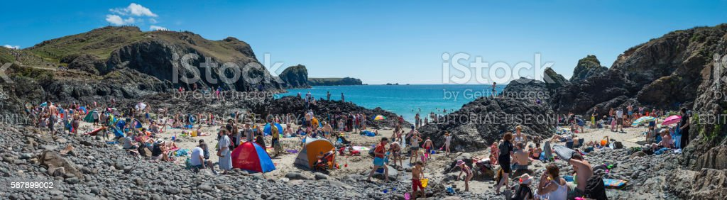 Families on crowded ocean beach summer holidays Kynance Cove Cornwall stock photo