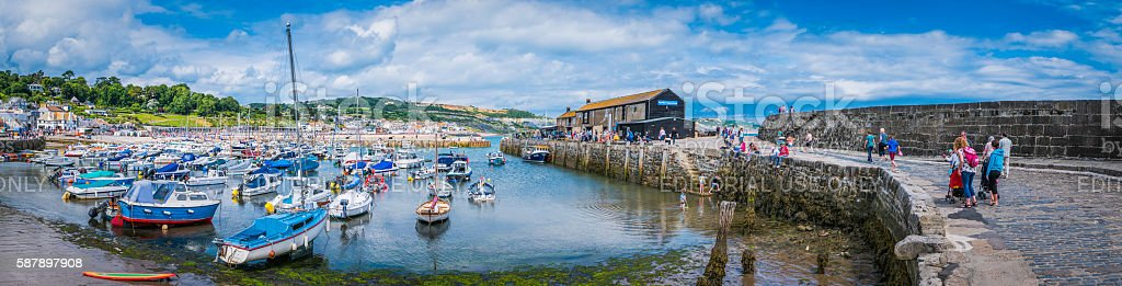 Families on holiday at seaside harbour Lyme Regis Cobb Devon stock photo