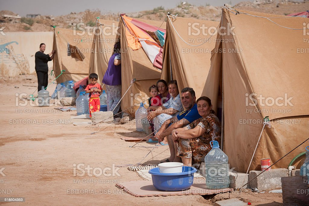 Families sitting in refugee camp stock photo