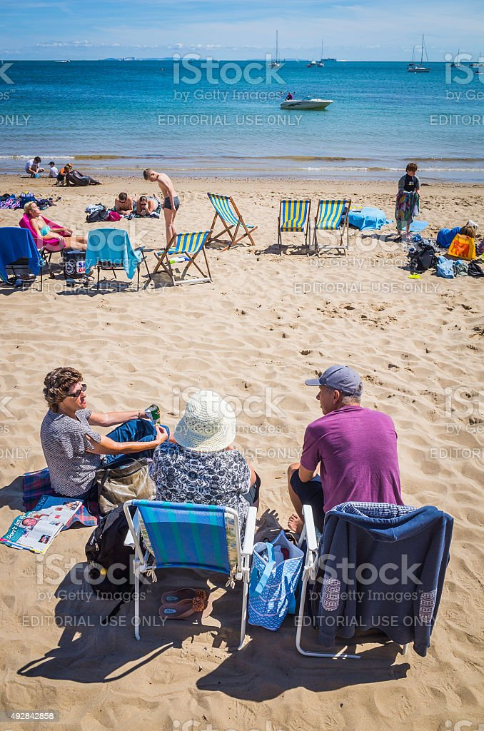Families tourists and daytrippers enjoying sunshine at seaside beach England stock photo