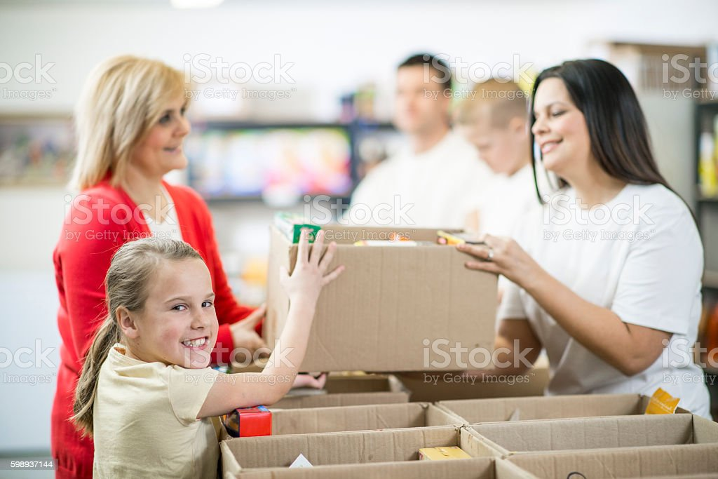 Families Volunteering Together in a Food Shelter stock photo