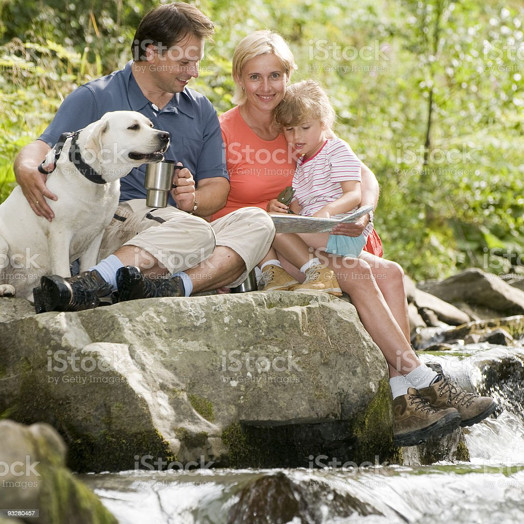 Family and dog hiking along river trail royalty-free stock photo