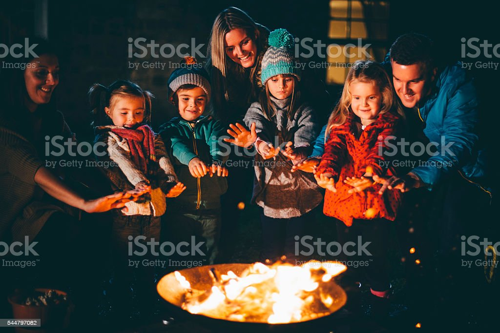 Family and Friends Gathered Around a Bonfire stock photo