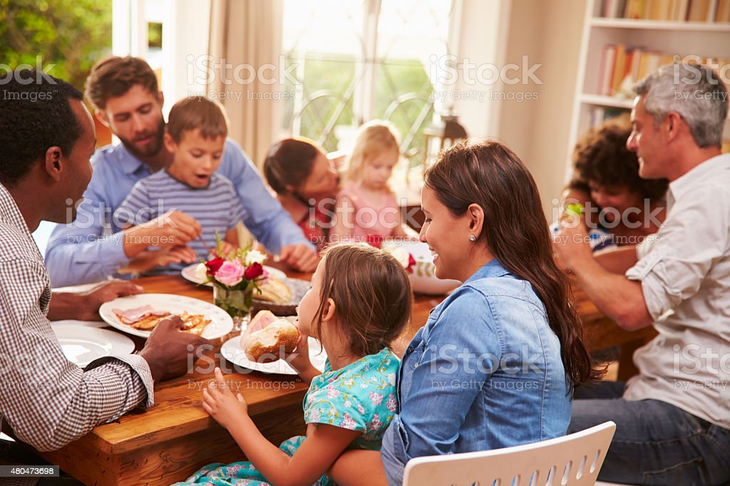 Family and friends sitting at a dining table stock photo