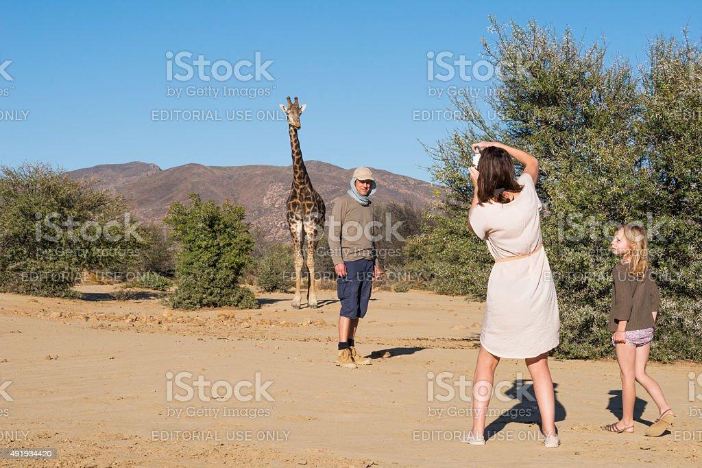 Family and giraffe on a walking safari stock photo
